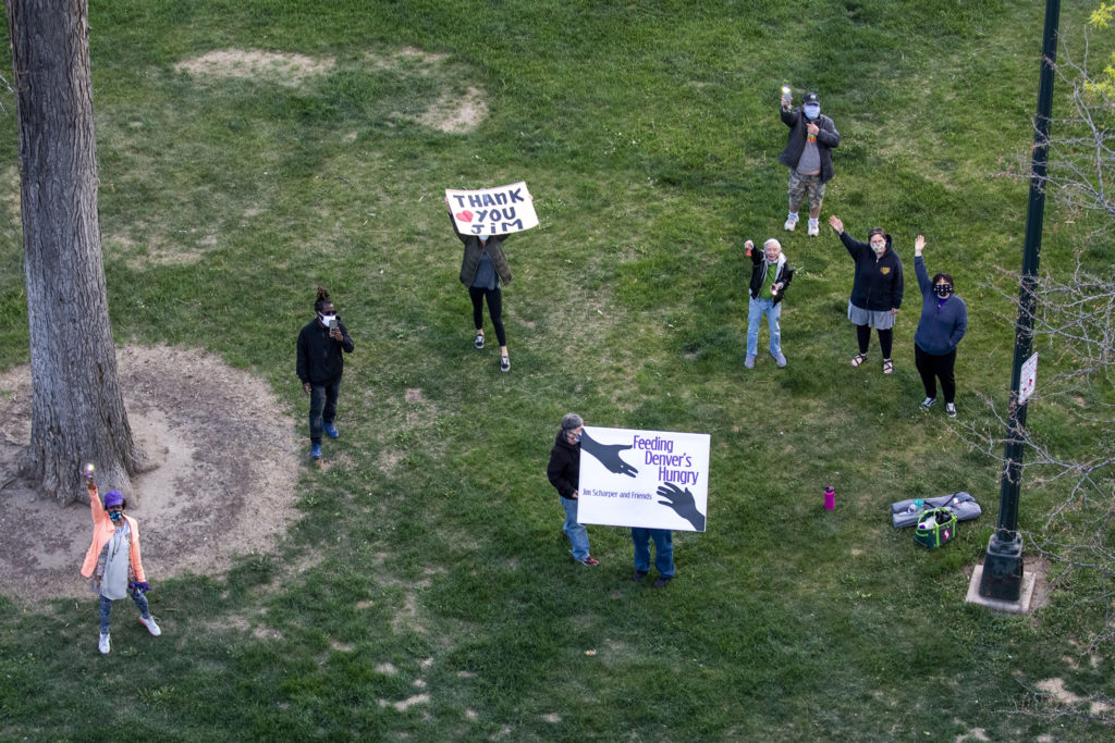 Jim Scharper's friends, many of whom help him at Feeding Denver's Hungry, wave to him from below as he plays music over Cheesman Park. May 7, 2020. (Kevin J. Beaty/Denverite)