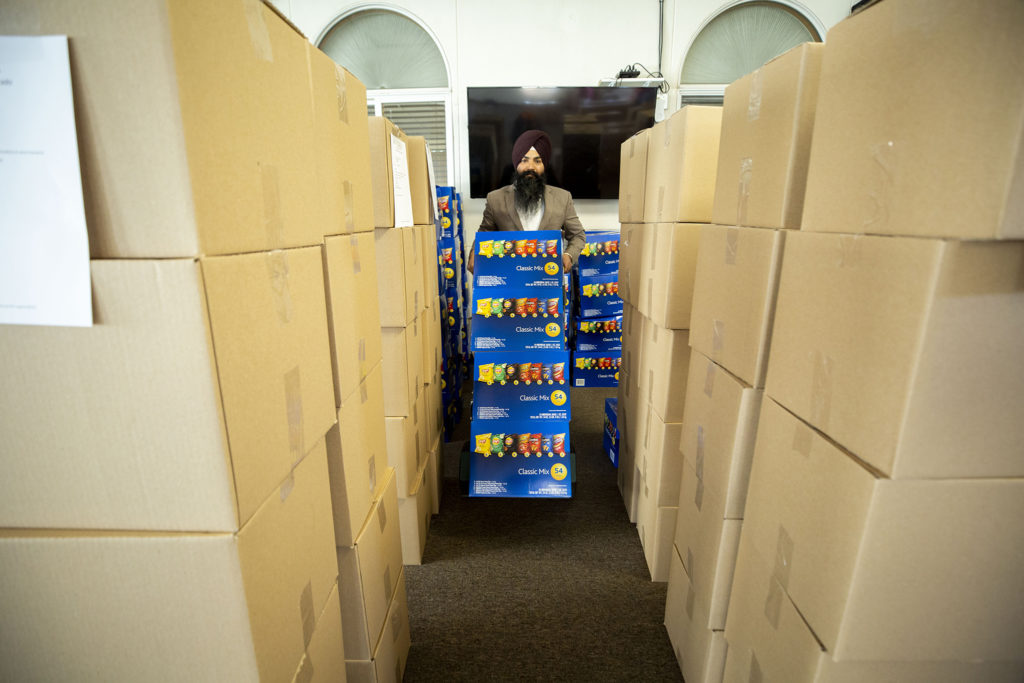 Davinder Sandhu carts boxes of snacks, packed here at Colorado Singh Sabha in Commerce City, to a truck bound for frontline workers around the state. May 8, 2020. (Kevin J. Beaty/Denverite)