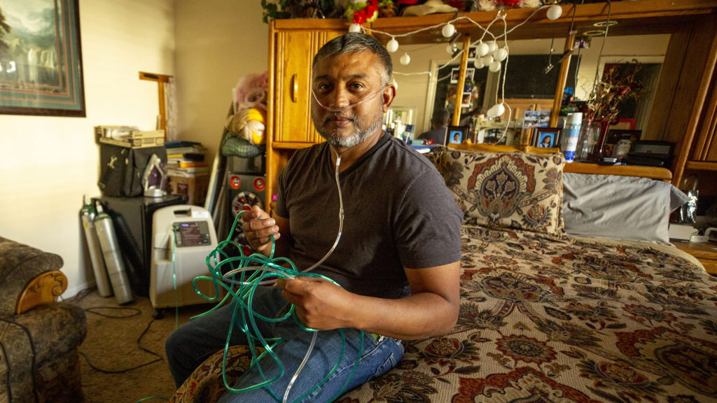 In his bedroom, David Puente wears the oxygen tube he needed while he was recovering from COVID-19. May 13, 2020. (Kevin J. Beaty/Denverite)