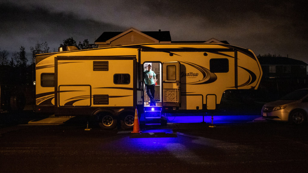 Bailey Queen stands in the RV trailer parked in front of his parents' Thornton home after a ten-hour shift working in an ambulance. May 15, 2020. (Kevin J. Beaty/Denverite)