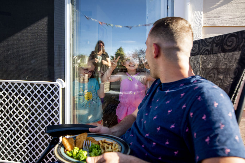 Bailey Queen makes faces at his sisters, Autumn and Amber, through a window while he eats dinner outside. It's a precaution to keep them safe, since he's an EMT who works with COVID-19 patients. Thornton, May 18. 2020. (Kevin J. Beaty/Denverite)