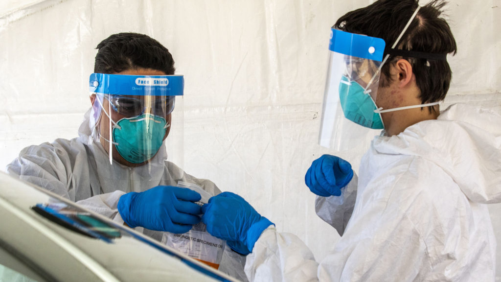 Worers process a COVID-19 swab at new mass testing facility at the Pepsi Center. May 21, 2020. (Kevin J. Beaty/Denverite)