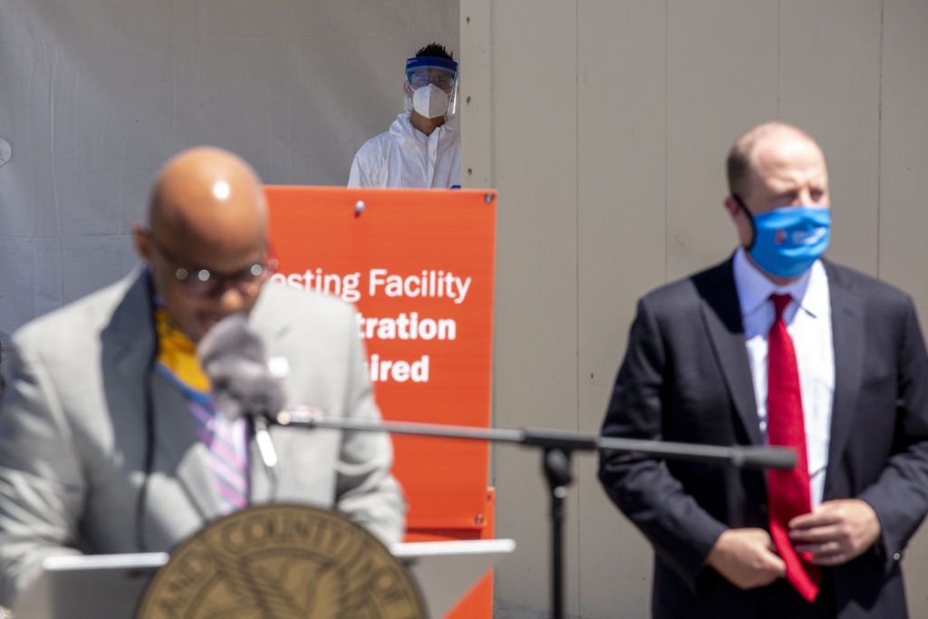 Takahiro Beachum, a Denver Police crime lab worker, watches from afar as Mayor Michael Hancock and Gov. Jared Polis announce a new mass testing facility for COVID-19 at the Pepsi Center. May 21, 2020. (Kevin J. Beaty/Denverite)