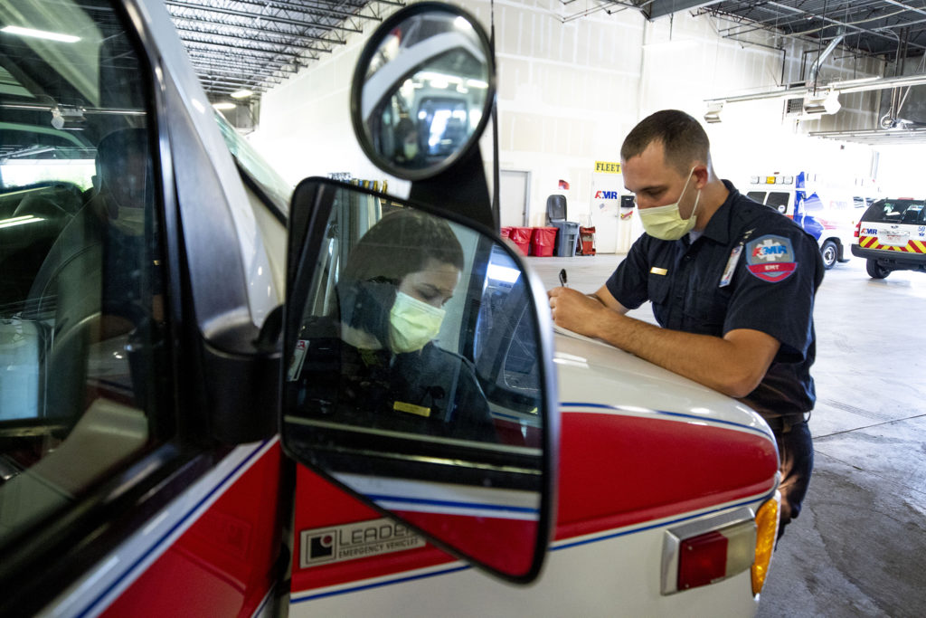 Bailey Queen and Chelsa Burrell preps their ambulance for a 10-hour shift at American Medical Response's headquarters in Arvada. May 22, 2020. (Kevin J. Beaty/Denverite)