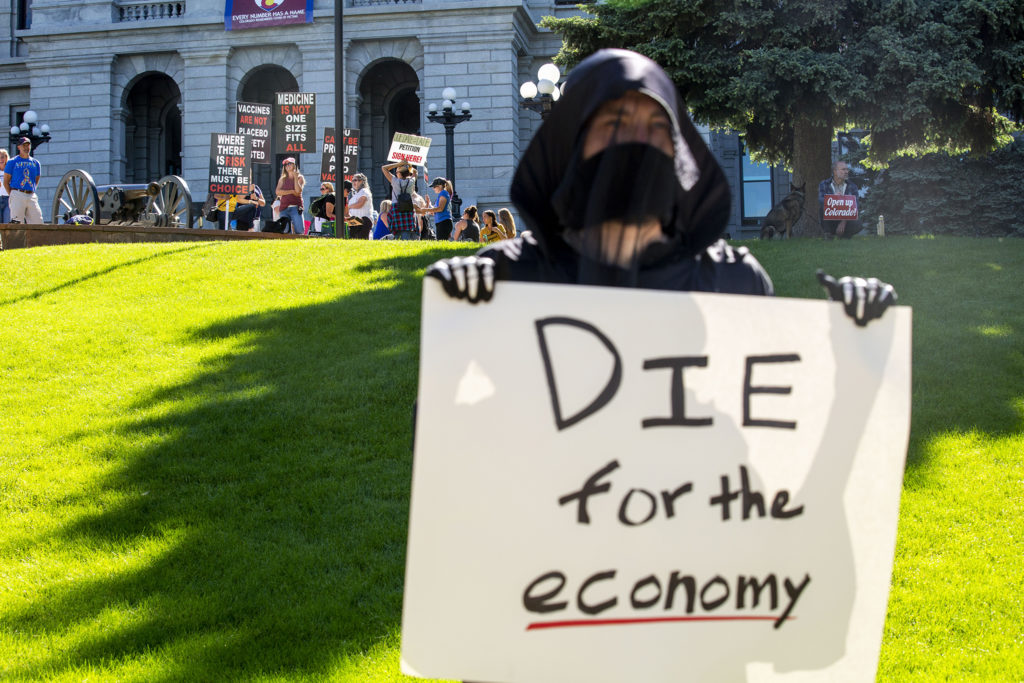 Protesters calling for a full re-opening of the state wait their turn to picket along Lincoln Street as Denver Democratic Socialists, dressed as grim reapers, protest a lack of eviction protections. May 26, 2020. (Kevin J. Beaty/Denverite)