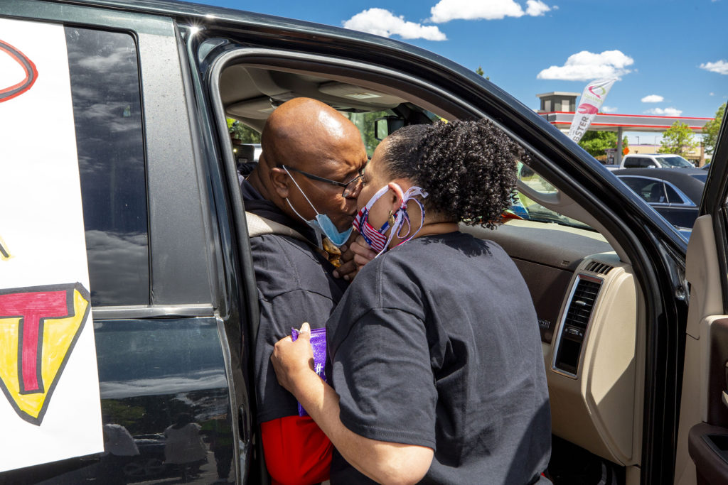 Pastor Terrance Hughes kisses his wife, Rachel. It's the second time they've seen each other in three months since he was diagnosed with COVID-19. May 27, 2020. (Kevin J. Beaty/Denverite)