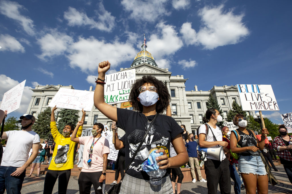 Celina Robinson holds up a fist as a protest at the Capitol begins in reaction to the death of George Floyd. May 28, 2020. (Kevin J. Beaty/Denverite)