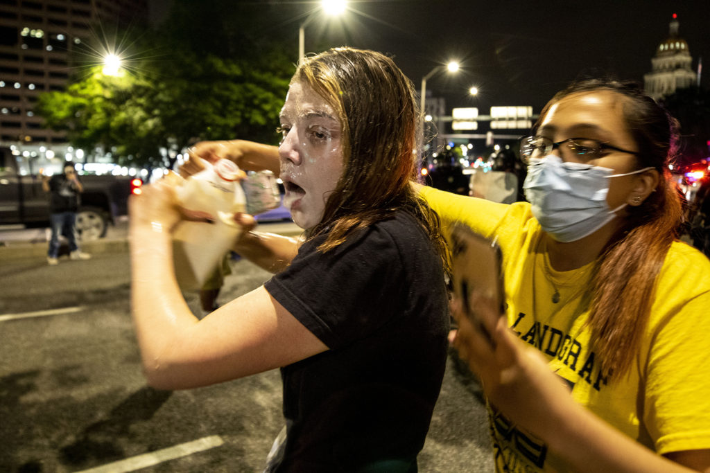 A woman pours milk on her face after Denver police hit her with pepper spray at close proximity during protests in reaction to the killing of George Floyd. May 28, 2020. (Kevin J. Beaty/Denverite)