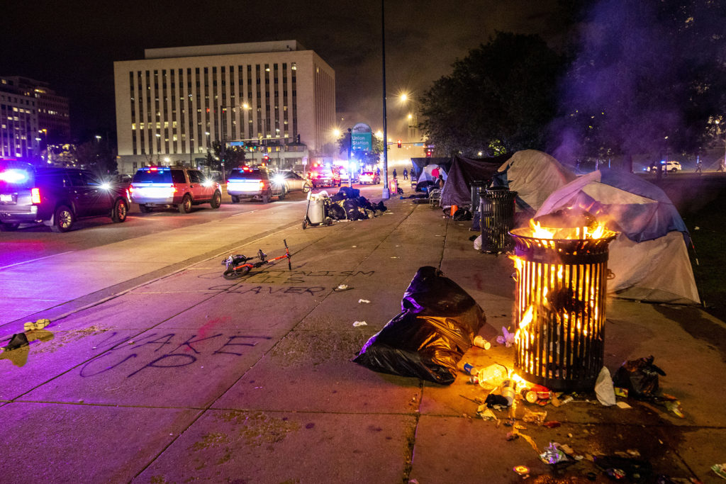 A trashcan at the corner of Broadway and Colfax Avenue burns as protesters react to the killing of George Floyd in Minnesota. May 28, 2020. (Kevin J. Beaty/Denverite)