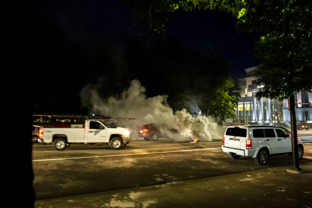 A Denver Police protest deterrent burns in the middle of Broadway as traffic continues (almost) as normal. May 29, 2020. (Kevin J. Beaty/Denverite)