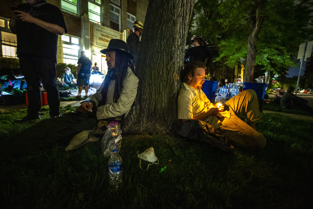 A man who said his name is Ananse Kuumma smokes against a tree back at Dorian Gray's base camp at 10th Avenue and Sherman Street. May 30, 2020. (Kevin J. Beaty/Denverite)