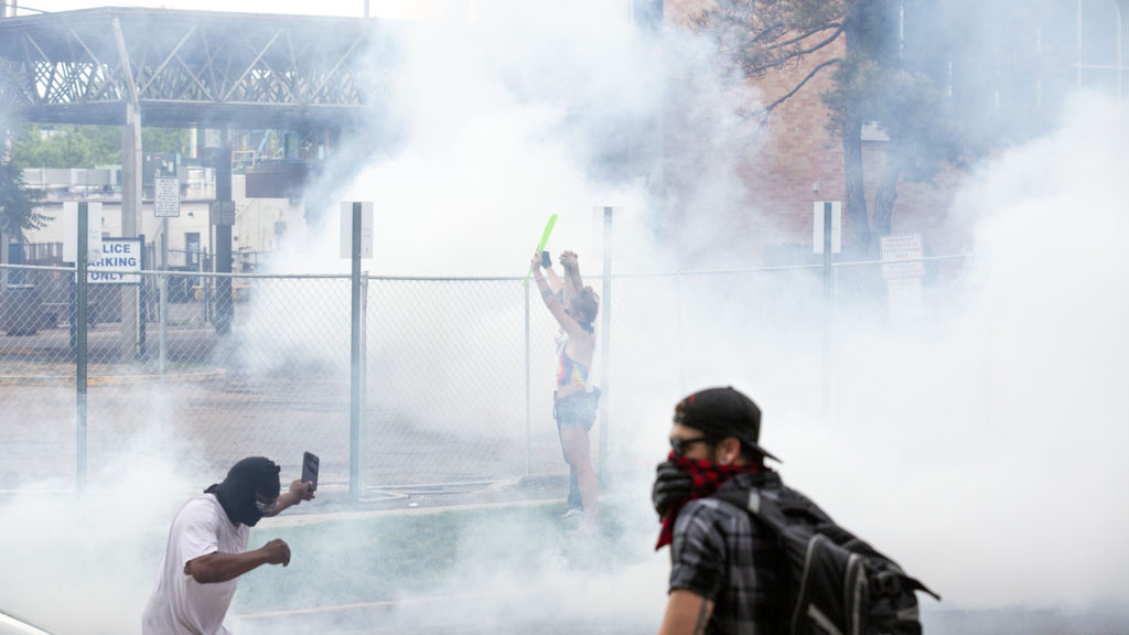 Officers covered a crowd surrounding Denver Police District Six's headquarters with tear gas on the third day of protests in reaction to the killing of George Floyd. May 30, 2020. (Kevin J. Beaty/Denverite)