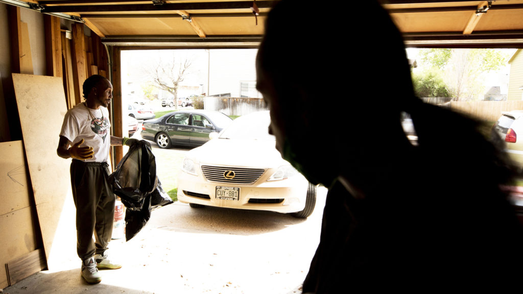 "Joel Hodge and his ""little"" brother-in-law, Eris Griffin, in Hodge's Montbello garage on a Saturday when he's waiting for a call from Denver Police to direct him to the family of a shooting victim who he plans to visit. May 17, 2020. (Kevin J. Beaty/Denverite)"