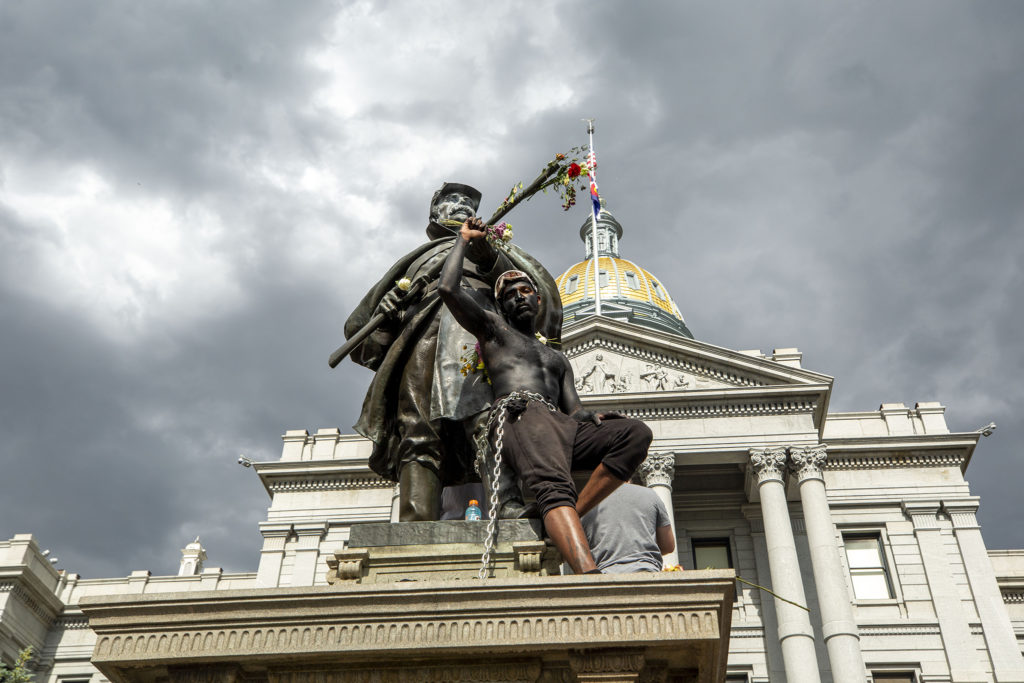 Jovan Brock chained himself to the statue by the west steps on the sixth day of protests in reaction to the killing of George Floyd by Minneapolis police. June 2, 2020. (Kevin J. Beaty/Denverite)