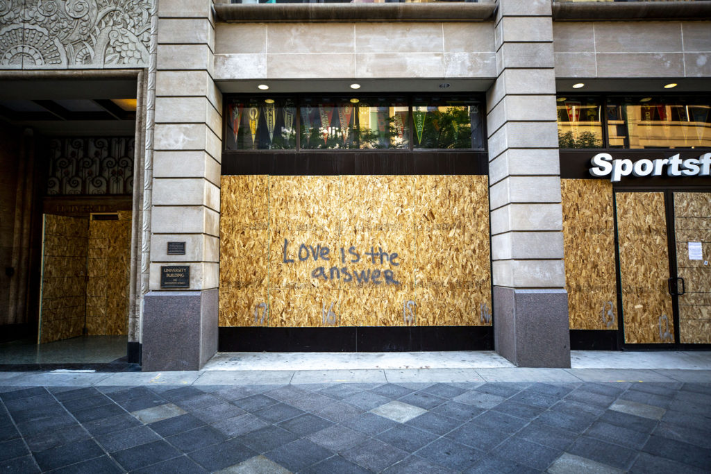 """Love is the answer"" painted on plywood covering a 16th Street Mall business. June 2, 2020. (Kevin J. Beaty/Denverite)"