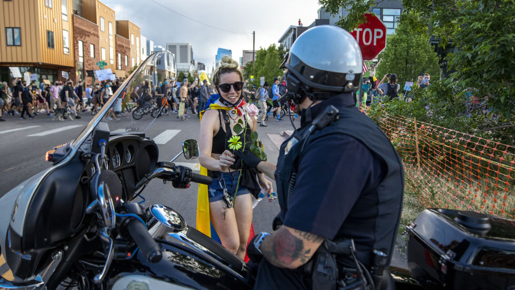 Ana Formoza hands a flower to a Denver Police officer on the sixth day of protests in reaction to the killing of George Floyd by Minneapolis police. June 2, 2020. (Kevin J. Beaty/Denverite)