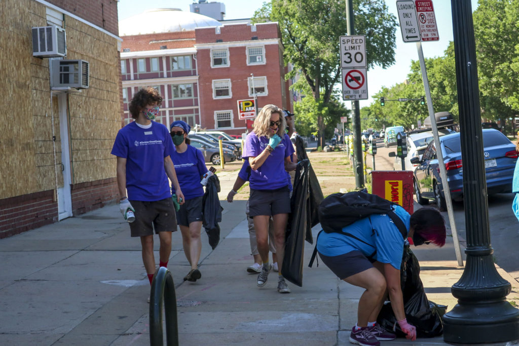 Volunteers clean up after a night of protests. (Jenny Brundin/CPR News)