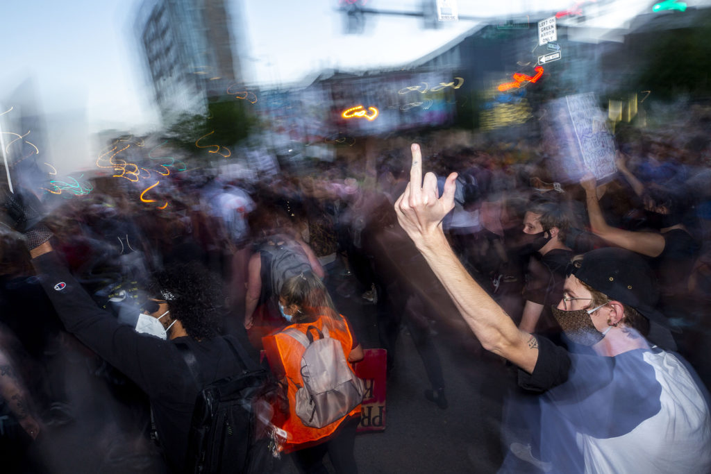 A man points his middle finger toward police officers as protests against police brutality continued on Saturday, June 7, 2020. (Kevin J. Beaty/Denverite)