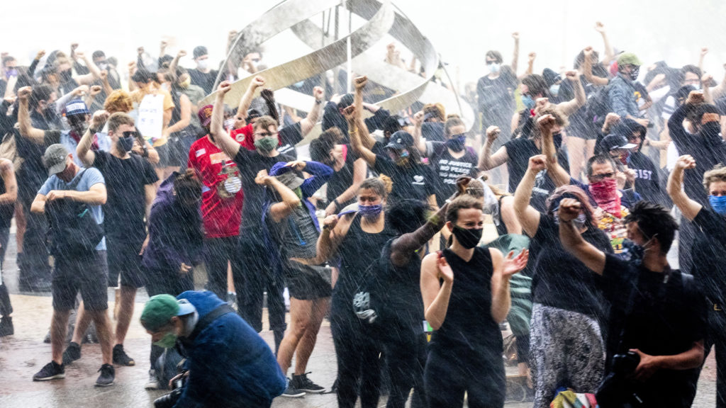 Protesters stay put with fists raised despite a torrential downpour during a rally against police brutality at the Aurora Municipal Center. June 6, 2020. (Kevin J. Beaty/Denverite)