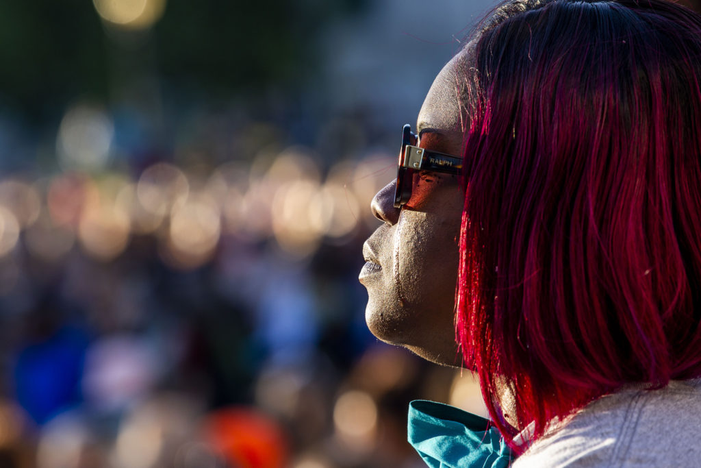 A tear falls from Melanie Crumb's cheek during a guided meditation exercise at the beginning of a vigil for George Floyd on the day of his burial at Civic Center Park. June 9, 2020. (Kevin J. Beaty/Denverite)