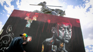Artist Kierre Dawkins works on a mural depicting the experience of young Black men in the United States, in Civic Center Park on Thursday, June 11, 2020.