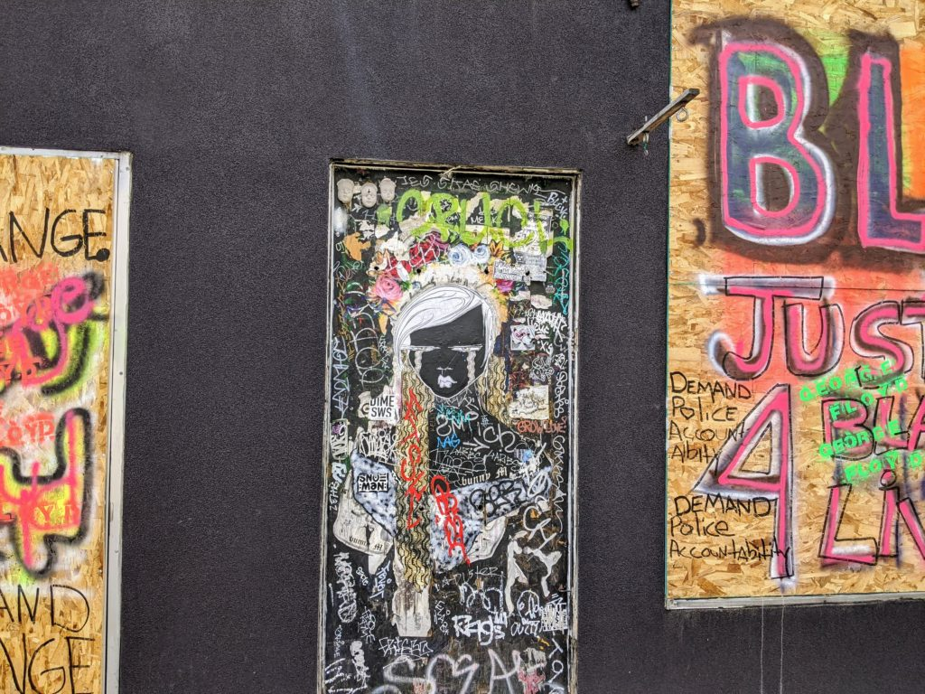 A painting by bunny M amid political graffiti in Denver on June 16, 2020. (Donna Bryson/Denverite)