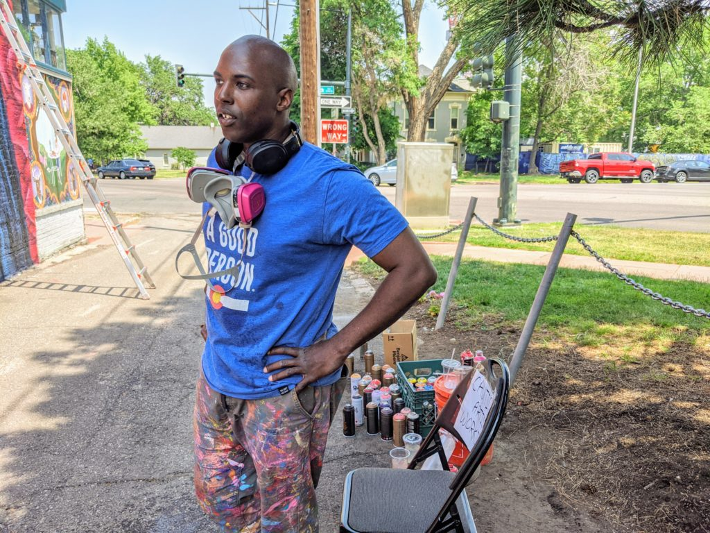 Artist Thomas Evans, known as Detour, pauses while working on his mural on June 17, 2020. (Donna Bryson/Denverite)