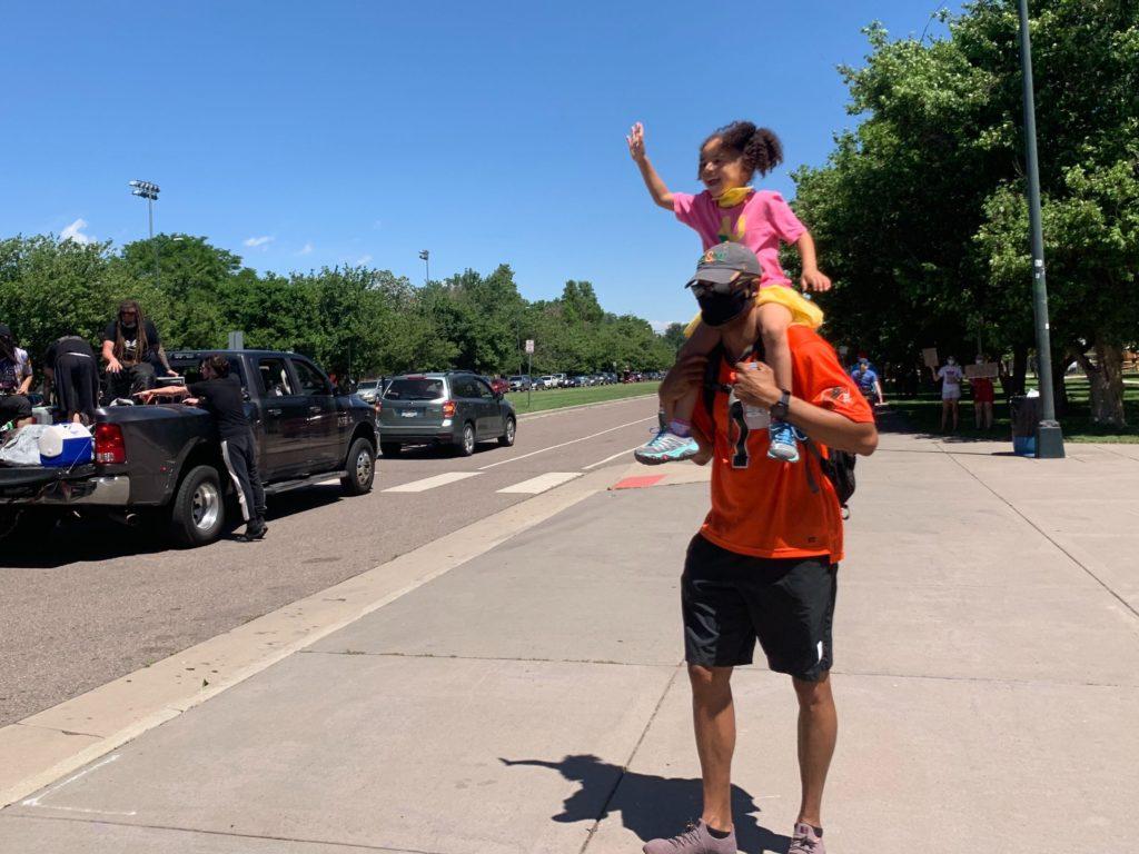 Anthony Ware carries his daughter, Aria, while taking part in a Black Lives Matter march on Sunday, June 7, 2020, in Denver. (Esteban L. Hernandez/Denverite)