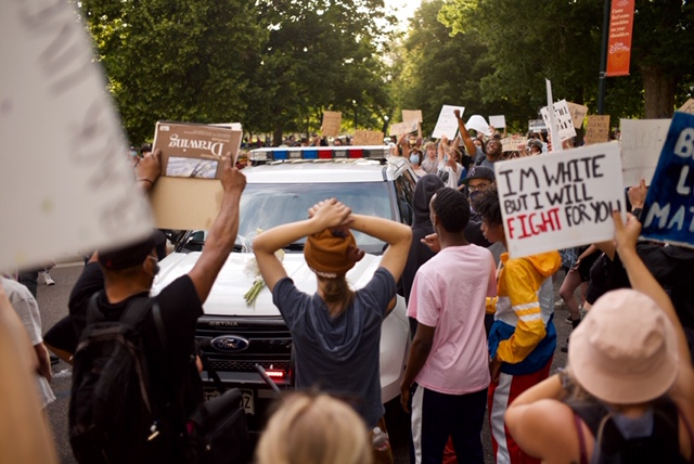 Peaceful protesters surround a Denver Police Department SUV in the middle of Lincoln Street on Monday, June 8, 2020. (Carl Glenn Payne/For Denverite)