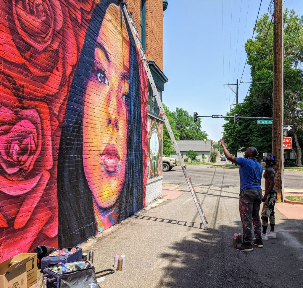 Artists Thomas Evans, known as Detour, and  Hiero Veiga confer as they work on a mural on June 17, 2020. (Donna Bryson/Denverite)