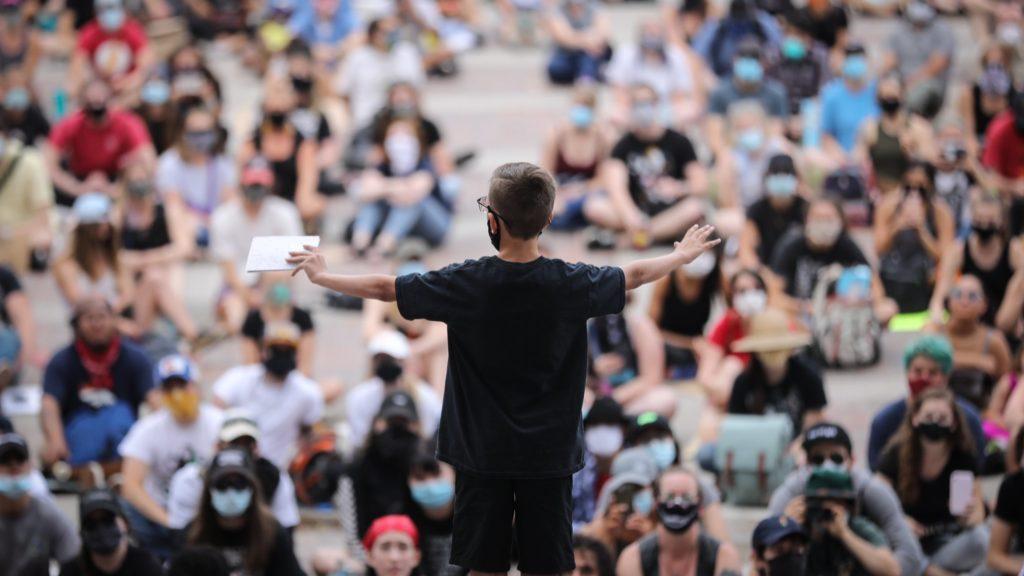 Tavien Woods, 14, of Denver, speaks to protesters on Thursday in Civic Center Park in Denver.