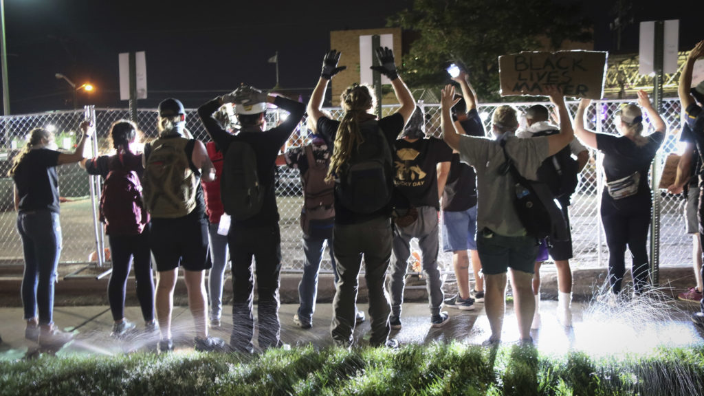 """Protesters hold up their hands and chant """"I can't breathe"""" at the Denver Police Department's District Six building off Colfax Avenue on Friday, June 5, 2020."""