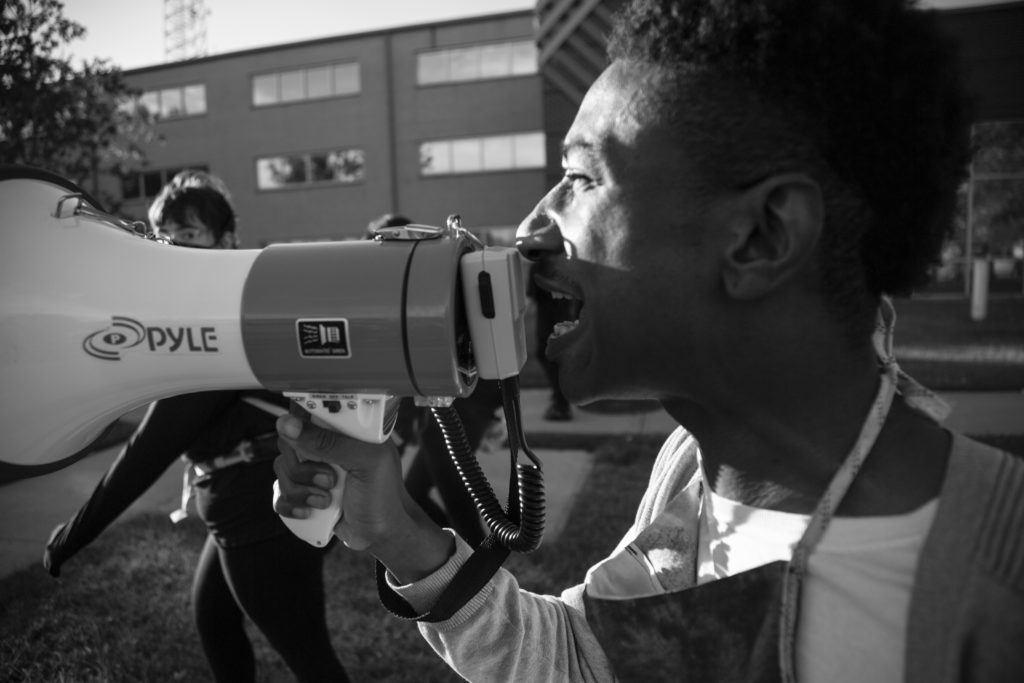 A demonstrator leads chants through a bull horn at a protest in memory of Elijah McClain on July 3, 2020.