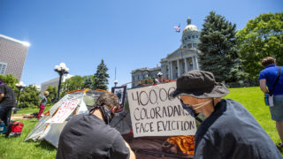 Kevin Breidenbach and Luke Wierman post signs to tents as the Denver Democratic Socialists of America protest rent and evictions as the economy continues to struggle under the pandemic. July 1, 2020. (Kevin J. Beaty/Denverite)