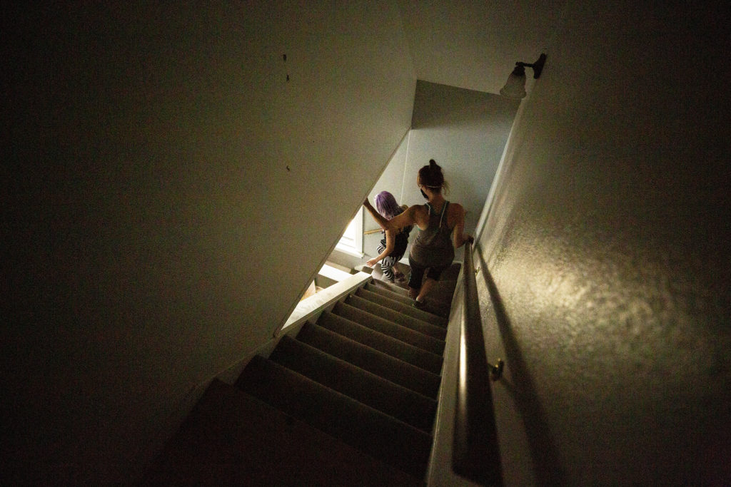Amber Blais and Staza Stone walk down the steps inside 4345 Tennyson Street, which they're turning into a performance space. Berkeley, July 2, 2020. (Kevin J. Beaty/Denverite)