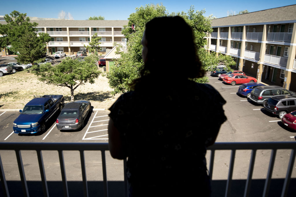 Stephanie Benites stands outside of the HomeTowne Studios motel room in Lakewood, one of the motels where she's been staying with her fiancé and daughter since they left Arizona fearing eviction. July 11, 2020. (Kevin J. Beaty/Denverite)