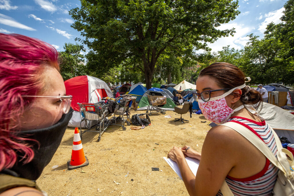 Belle Ruocco (left) and Magdalena Franchois survey an encampment at Lincoln Park, at Lincoln Street and Colfax Avenue, as part of Denver Homeless Out Loud's count of unhoused residents in the city. July 17, 2020.