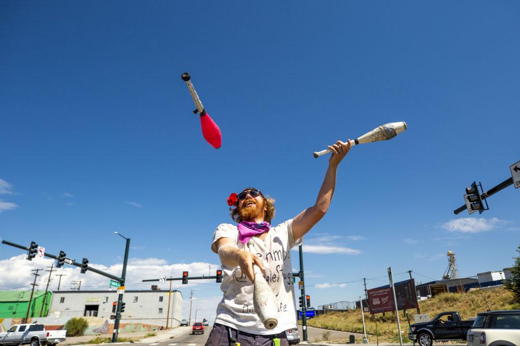 Eric Bogel, AKA JuggleStruggle, performs for tips during red lights at a Baker intersection. July 17, 2020.