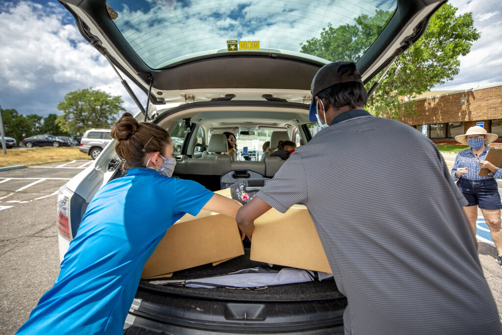 Robyn Hills (left) helps load boxes of food into Michele Andersen's car outside of the Southwest Family YMCA. July 24, 2020.