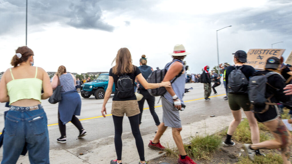 A driver in a blue Jeep speeds through a protest demanding justice for Elijah McClain. A protester fired a gun as the vehicle drove by, shooting other protesters on July 25, 2020.