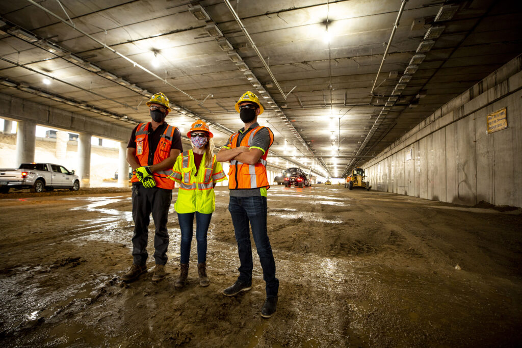 Tanner Peyton (left to right), Stacia Sellers and Matt Sanman stand inside the future, capped section of I-70 that will eventually channel cars below grade through Elyria Swansea. July 28, 2020.