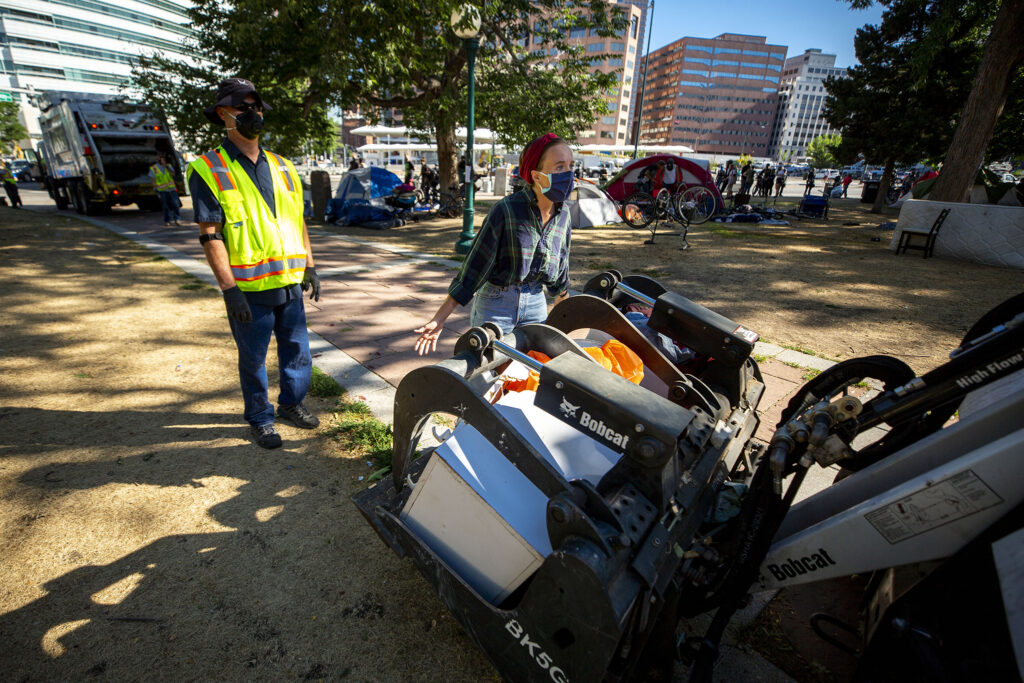 A protester attempts to stop city officials from conducting a forced cleanup of encampments at Lincoln Park, across Lincoln Street from the Capitol. July 29, 2020.