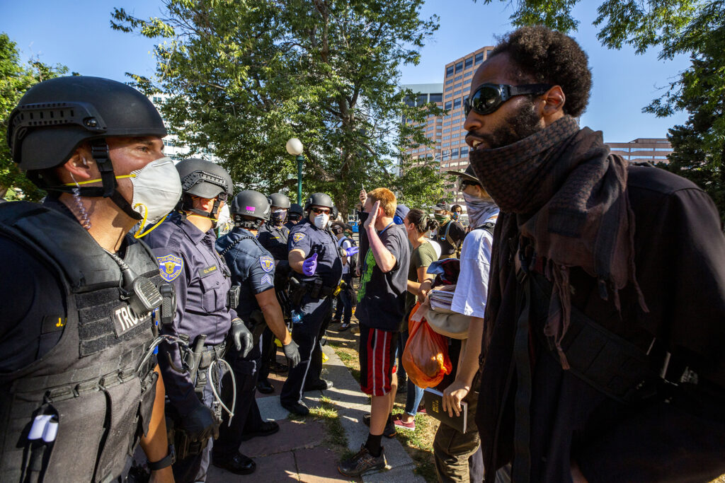 Gabriel Lavine argues with state police officers helping city officials conduct a forced cleanup of encampments at Lincoln Park, across Lincoln Street from the Capitol. July 29, 2020.