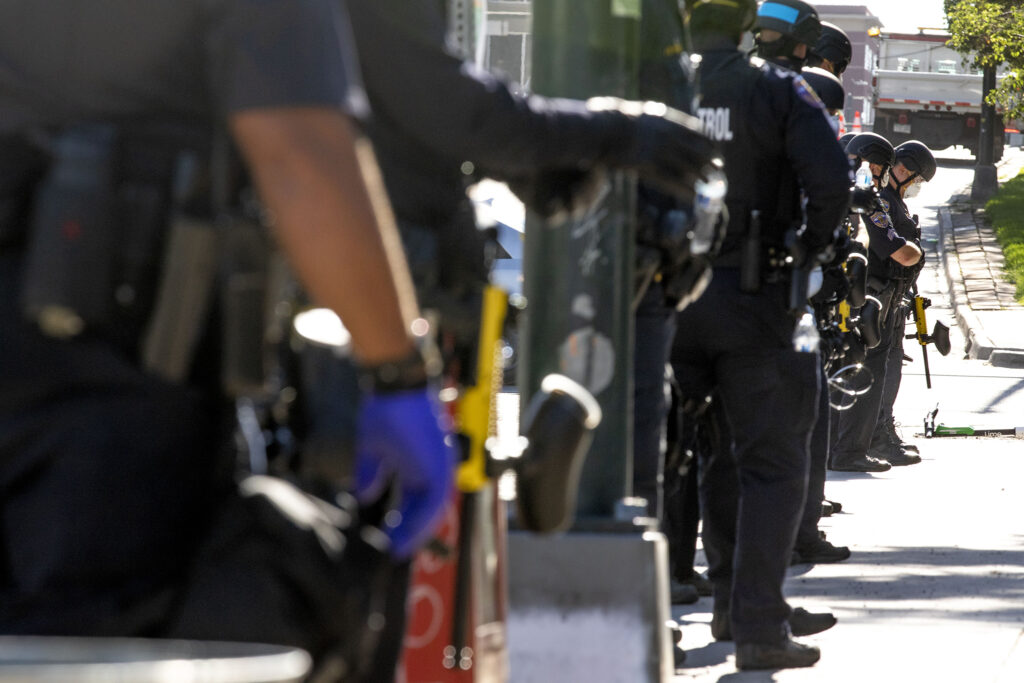 State police officers stand ready with nonlethal munitions as city officials conduct a forced cleanup of encampments at Lincoln Park, across Lincoln Street from the Capitol. July 29, 2020.