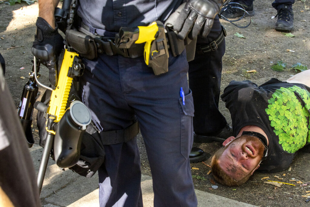 State police detain Timothy Wempen, who was protesting a forced cleanup of encampments at Lincoln Park, across Lincoln Street from the Capitol. July 29, 2020.