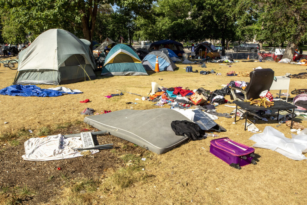 Belongings are strewn on the grass in Lincoln Park as city officials conduct a forced cleanup of encampments here, across Lincoln Street from the Capitol. July 29, 2020.