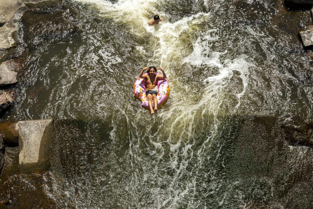 Cristian Vazquez floats the South Platte River into Confluence Park atop a doughnut tube. Aug. 12, 2020.