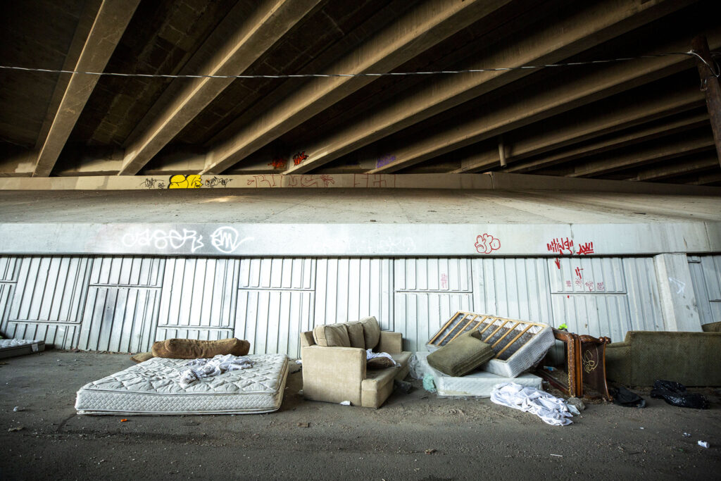 Mattresses and couches are gathered beneath an I-70 overpass between railroad tracks and the National Western Center. Aug. 15, 2020.