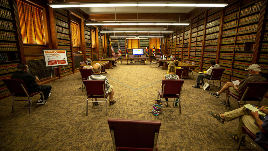 Residents watch on a TV as Denver's planning board meets elsewhere in the City and County Building, socially distanced, to discuss changes to group living rules. Aug. 19, 2020.