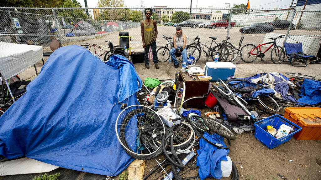 Alfredo Gomez (left) and Michael Meek hang out at the edge of an encampment along 22nd Street. Gomez has lived around here for about three months. Meek is living in the Aloft Denver Downtown hotel, which opened as an emergency shelter space when the pandemic began. Aug. 19, 2020.